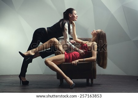 Beautiful lesbian flirting couple in the chair. - stock photo