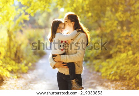 Beautiful lifestyle autumn photo mother and child walks evening in the park, warm sunlight - stock photo