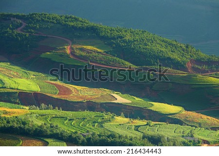 Beautiful light beam in morning with red soil and village on mountain valleys at Hongtudi,Dongchuan, Yunnan,Kunming of China - stock photo