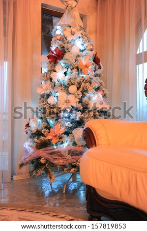 Beautiful lighted christmas tree in cozy home  - stock photo