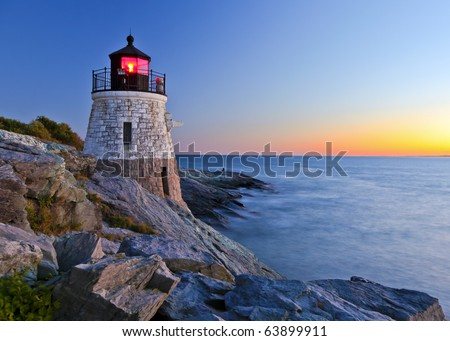 Beautiful lighthouse by the ocean at sunset - stock photo