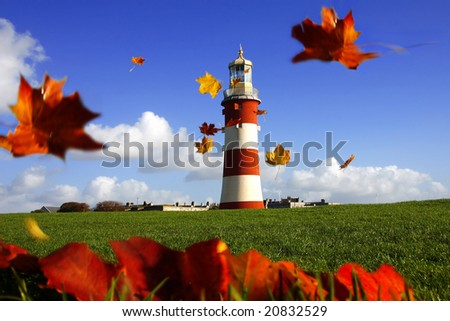 beautiful lighthouse with flying autumn  leaves - stock photo