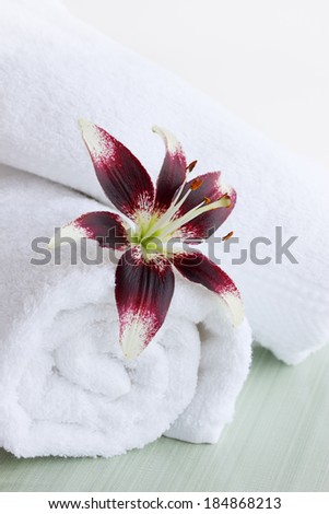 Beautiful lily and white fluffy towels, spa still life - stock photo