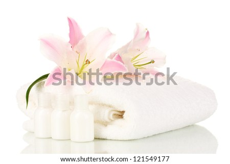 beautiful lily with towel and bottles isolated on white - stock photo