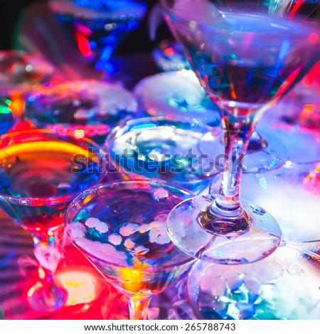 Beautiful line of different colored cocktails with smoke on a open air party, tequila, martini, vodka, and others on decorated catering bouquet table on open air party with smoke - stock photo