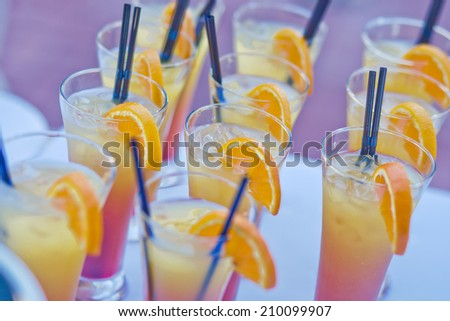 Beautiful line of different coloured cocktails on a open air party, tequila, martini, vodka, and others on decorated catering bouquet table on open air party  - stock photo