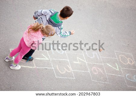 beautiful litlle boy and girl on the hopscotch - stock photo