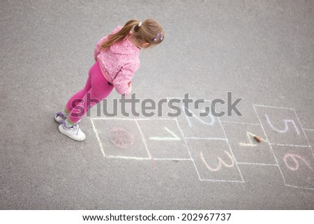 beautiful litlle girl on the hopscotch - stock photo