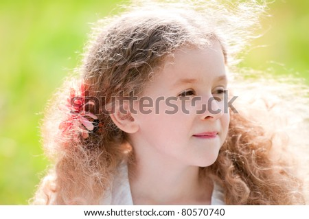 beautiful little and happy girl smiling. Summer park in background. - stock photo