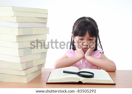 Beautiful little and serious asian girl reading book. - stock photo