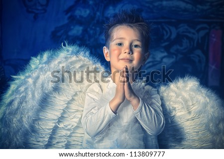 Beautiful little angel boy over Christmas background. - stock photo
