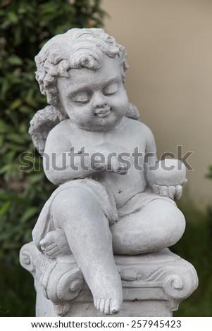 Beautiful little angel statue in garden ,hand focus - stock photo