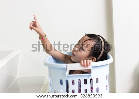 Beautiful little asian girl  playing in blue basket - stock photo