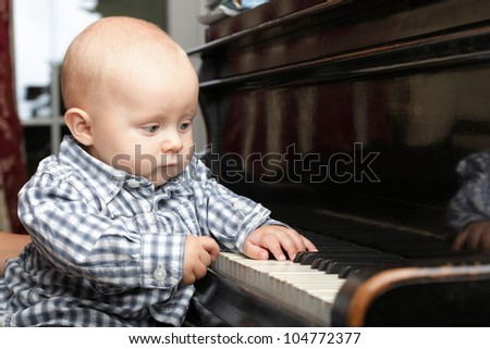 beautiful little baby boy learning plays piano - stock photo