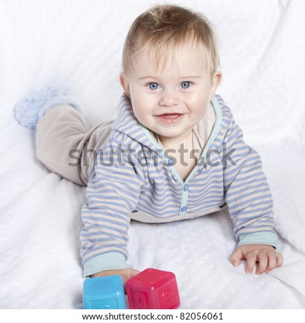 Beautiful little baby boy playing on white blanket with generic abc blocks 9 months old - stock photo