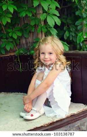 beautiful little baby girl sitting on bench in summer garden - stock photo