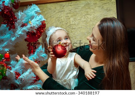 beautiful little baby girl with blue eyes decorates the Christmas tree with her mother. Christmas mood. new year. - stock photo