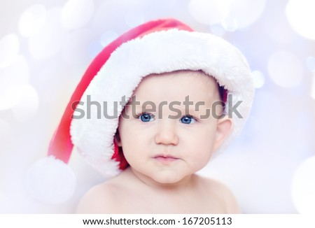 Beautiful little baby in Santa hat - stock photo