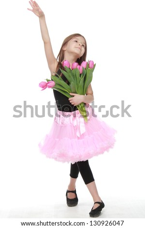 Beautiful little ballerina with long healthy hair in a pink tutu dancing ballet with tulips - stock photo
