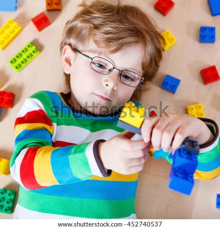 Beautiful little blond child with glasses playing with lots of colorful plastic blocks indoor. Happy Kid boy wearing colorful shirt and having fun with building and creating. - stock photo