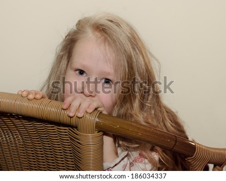 Beautiful little blond girl with long hair sitting peering over the back of a wicker chair at the camera with a quiet smile - stock photo