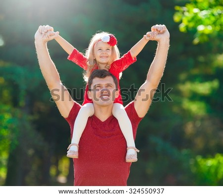 Beautiful little blonde girl and her father, has happy fun cheerful smiling face, red clothes. Family portrait nature.  - stock photo