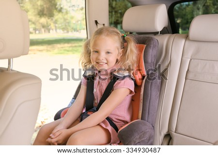 Beautiful little blonde sitting in the car - stock photo