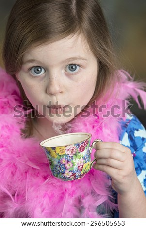 Beautiful little blue eyed girl with floral tea cup and pink feather boa - stock photo