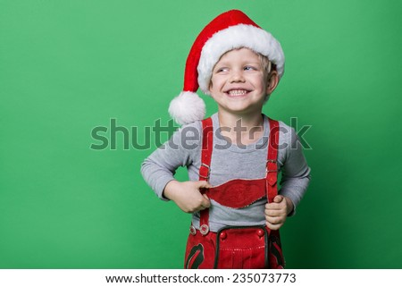 Beautiful little boy dressed like Christmas elf with big smile. Christmas concept. Studio portrait over green background    - stock photo