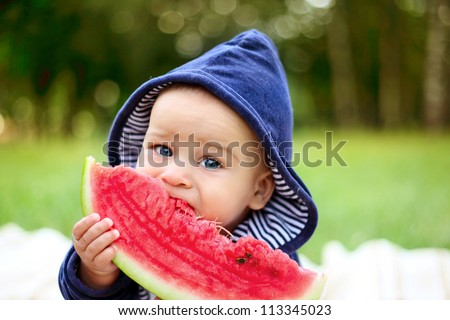 beautiful little boy eats ripe watermelon on the nature - stock photo