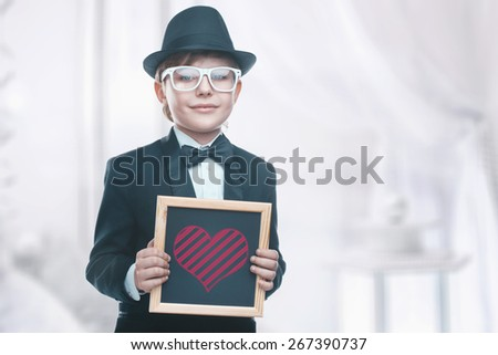 Beautiful little boy with a board. Looking at the camera. Drawing a heart. Valentine's day holiday - stock photo