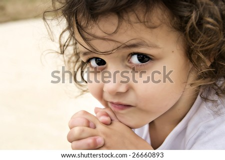 Beautiful little brown eyed brunette girl with curly hair thinking. - stock photo