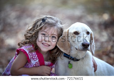 Beautiful little brunette girl hugging a friendly dog - stock photo
