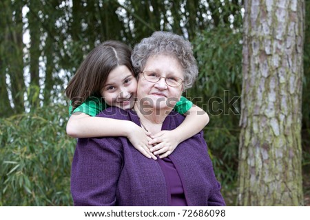 Beautiful little brunette girl hugging her Great Grandmother in outdoor wooded setting - stock photo