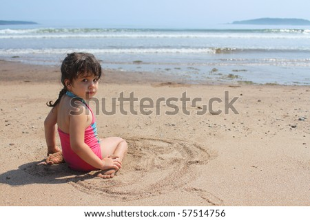 Beautiful little brunette girl in pink bathing suit sitting in the sand at New River beach, New Brunswick, Canada - stock photo