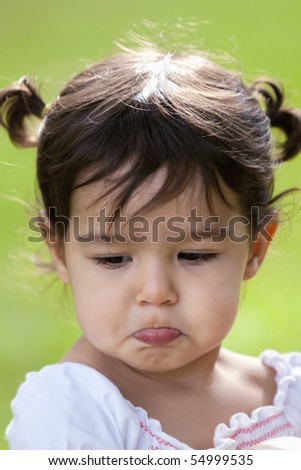 Beautiful little brunette girl with pigtails and a big pout on her face outdoors - stock photo