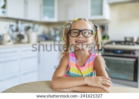 Beautiful little cheerful girl in glasses sitting at kitchen table. - stock photo