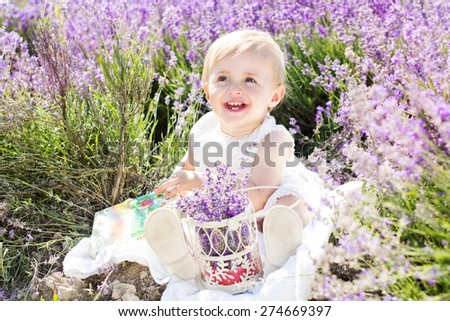 Beautiful little child girl is playing in a field of lavender purple flowers - stock photo