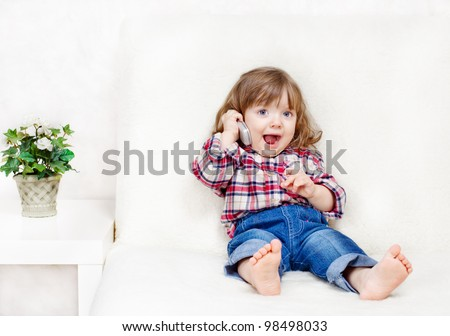 beautiful little child holds a cell phone - stock photo