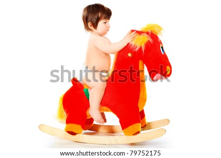 Beautiful little child riding her toy horse. Isolated over white. - stock photo