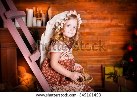 Beautiful little curly blonde girl, has happy fun cheerful smiling face, big blue eyes, white hat. Portrait holiday Christmas. Wooden room with fireplace and tree. - stock photo