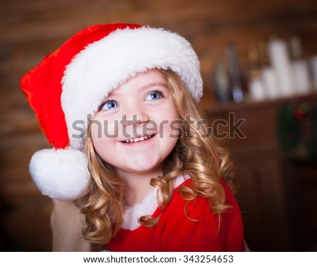Beautiful little curly blonde girl, has happy fun cheerful smiling face, blue eyes, red Christmas hat Santa Claus. Portrait holiday.  - stock photo