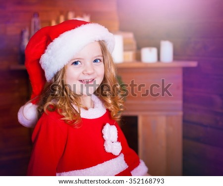 Beautiful little curly blonde girl, has happy fun cheerful smiling face, blue eyes, red Christmas hat. Portrait holiday.  - stock photo