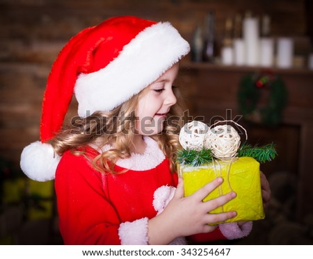 Beautiful little curly blonde girl, has happy fun cheerful smiling face profile, has red Christmas hat Santa Claus, holding a gift box. Portrait holiday.  - stock photo