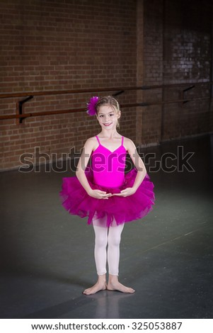 Beautiful little dancer portrait at a dance studio. Vertical photo in a traditional dance studio. Lots of copy space above - stock photo