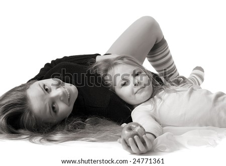 beautiful little daughter with apple lies on mum's stomach, isolated on white - stock photo