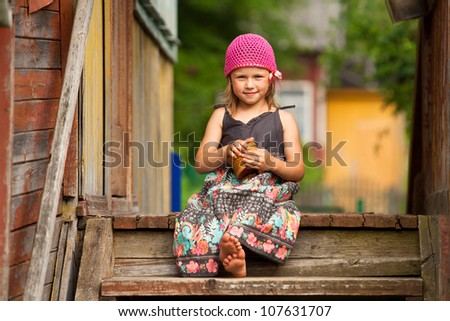 Beautiful little five-year girl on the porch of a village house - stock photo