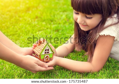 beautiful little girl and a woman hands holding small house on a background of green grass - stock photo