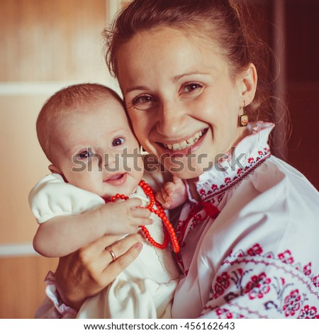 beautiful little girl and her mother smiling at the camera - stock photo