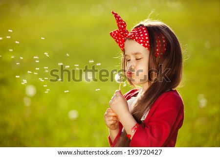 Beautiful little girl blowing dandelion. Happiness, fashionable concept. - stock photo